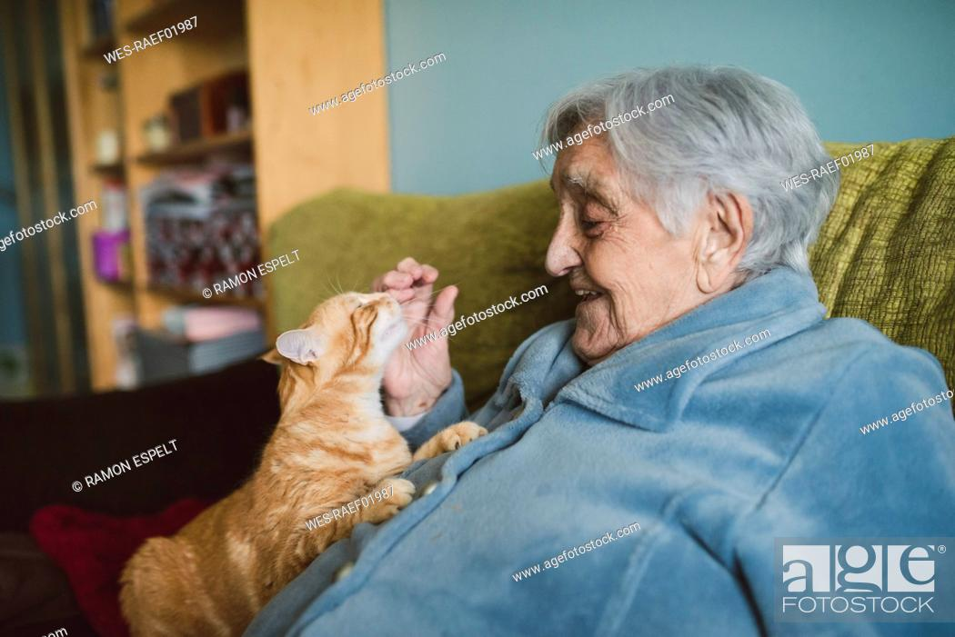 Stock Photo: Happy senior woman with tabby cat on the couch.