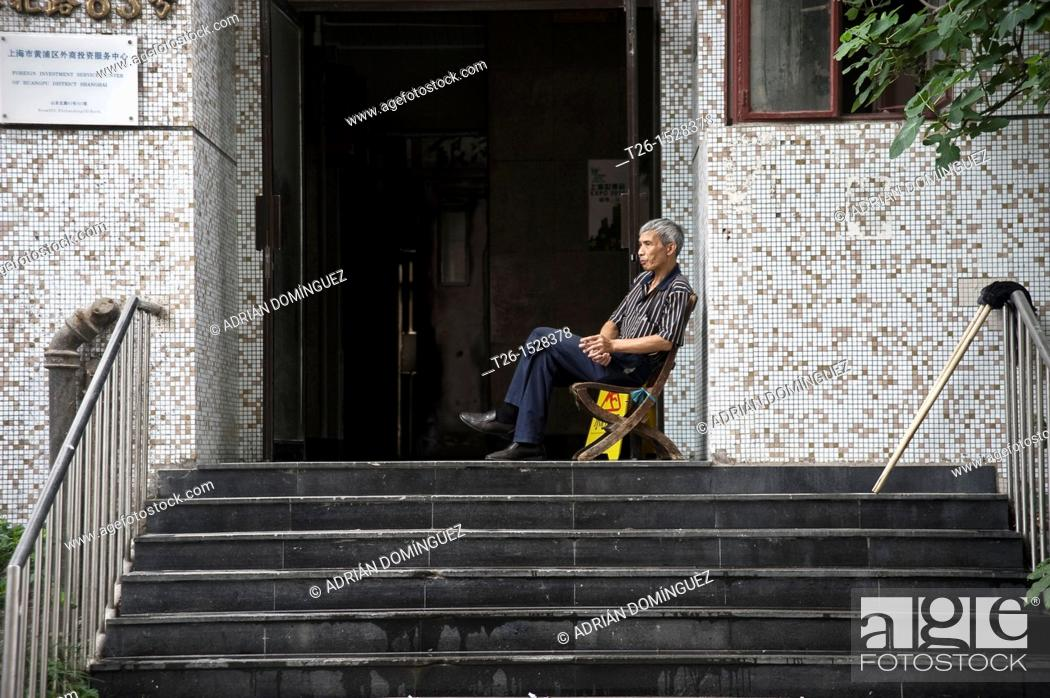 Stock Photo: Man sitting up step in Shanghai. China country.