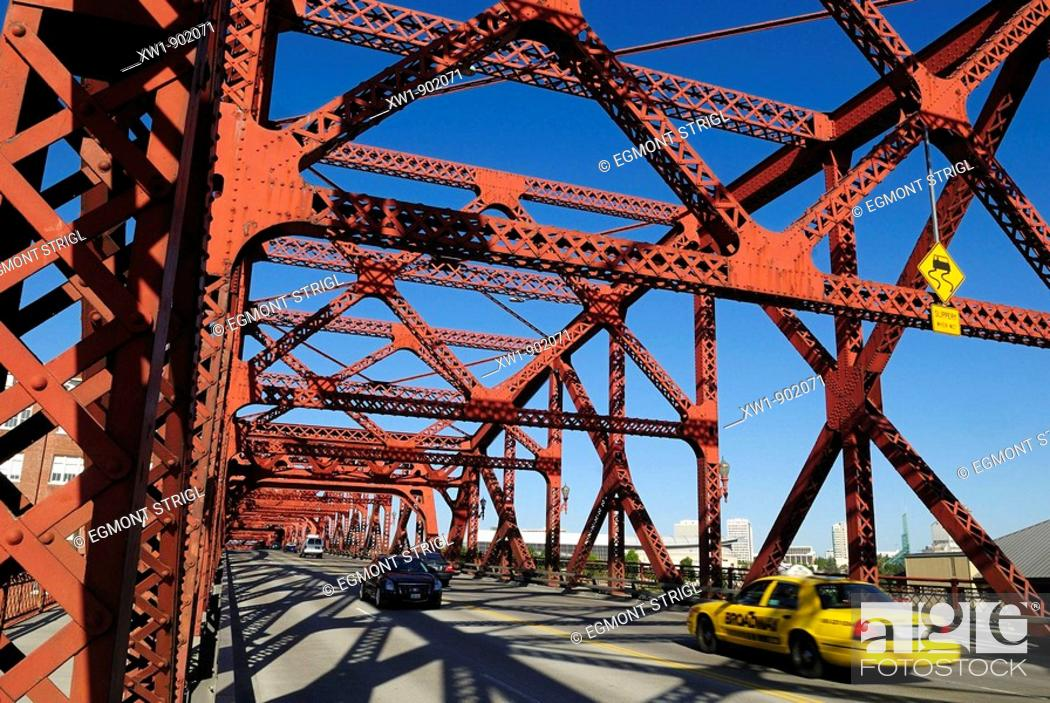 Stock Photo: yellow cab and cars crossing a historic steel bridge over Willamette River, Portland, Oregon, USA.
