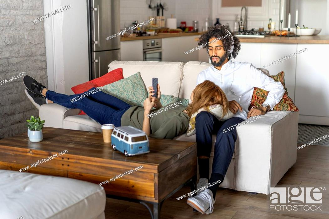 Stock Photo: Couple relaxing on couch, planning their road trip.