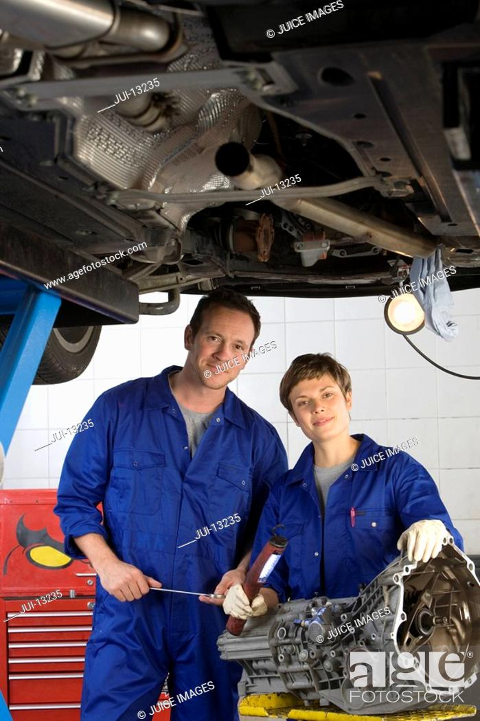 Stock Photo: Female mechanic and colleague by elevated car, smiling, portrait.