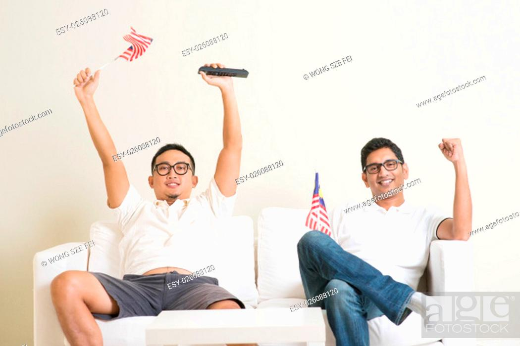 Stock Photo: Young men watching live sport television program at home, waving Malaysia flag shouting and celebrate.