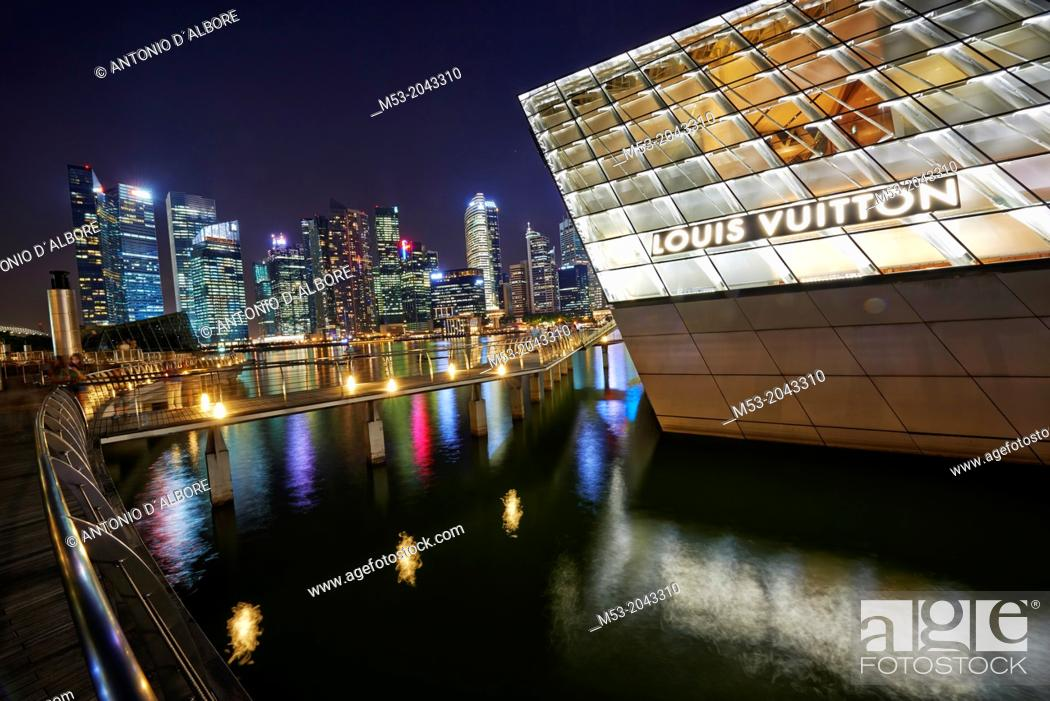 Stock Photo: The Loius Vuitton Island Maison, a luxury shop designed by architect Peter Marino located in Marina Bay. In the background the skyscrapes of the Central.