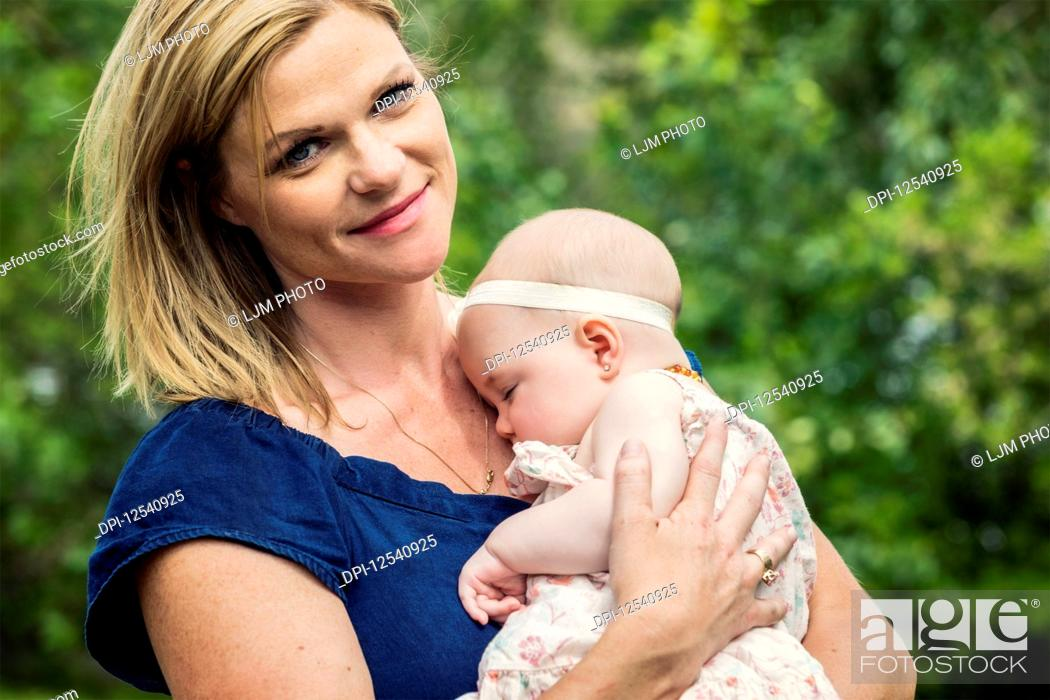 Stock Photo: A young mother cuddling her sleeping baby outdoors in a park; Edmonton, Alberta, Canada.