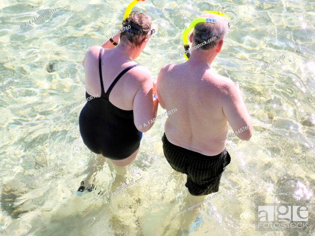Stock Photo: Retired tourist couple snorkeling on the beach. Sharm el-Sheikh, Egypt.