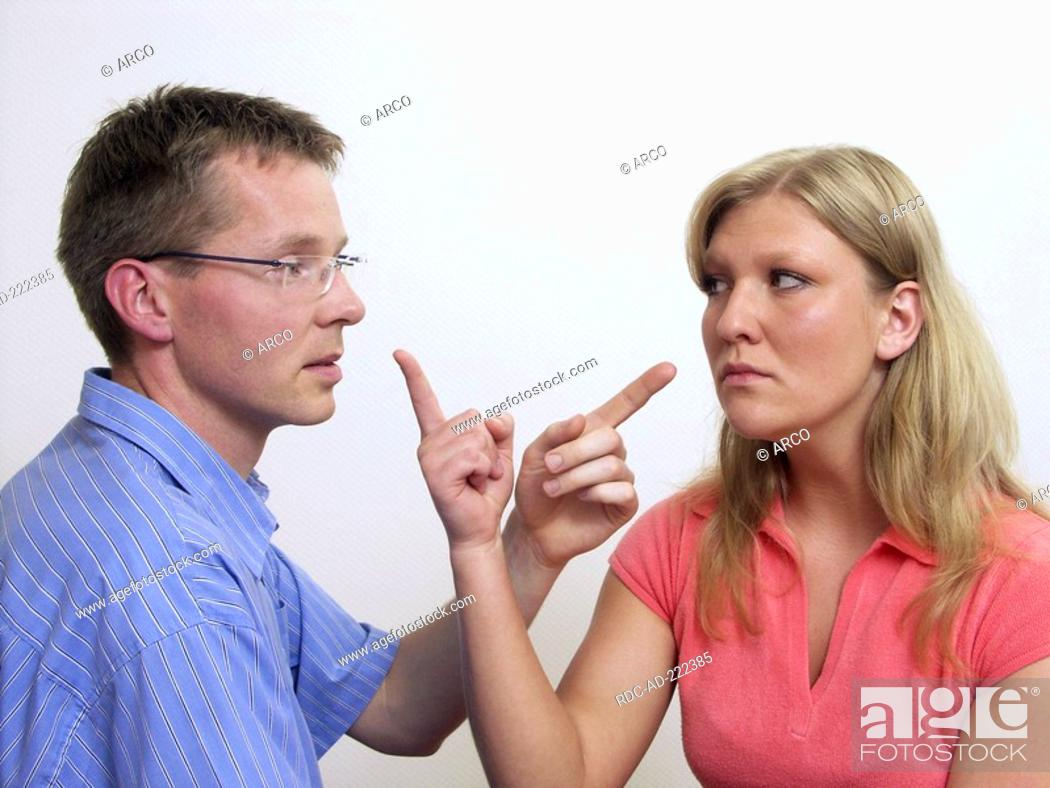 Young couple raising index finger, hint, negate, wife