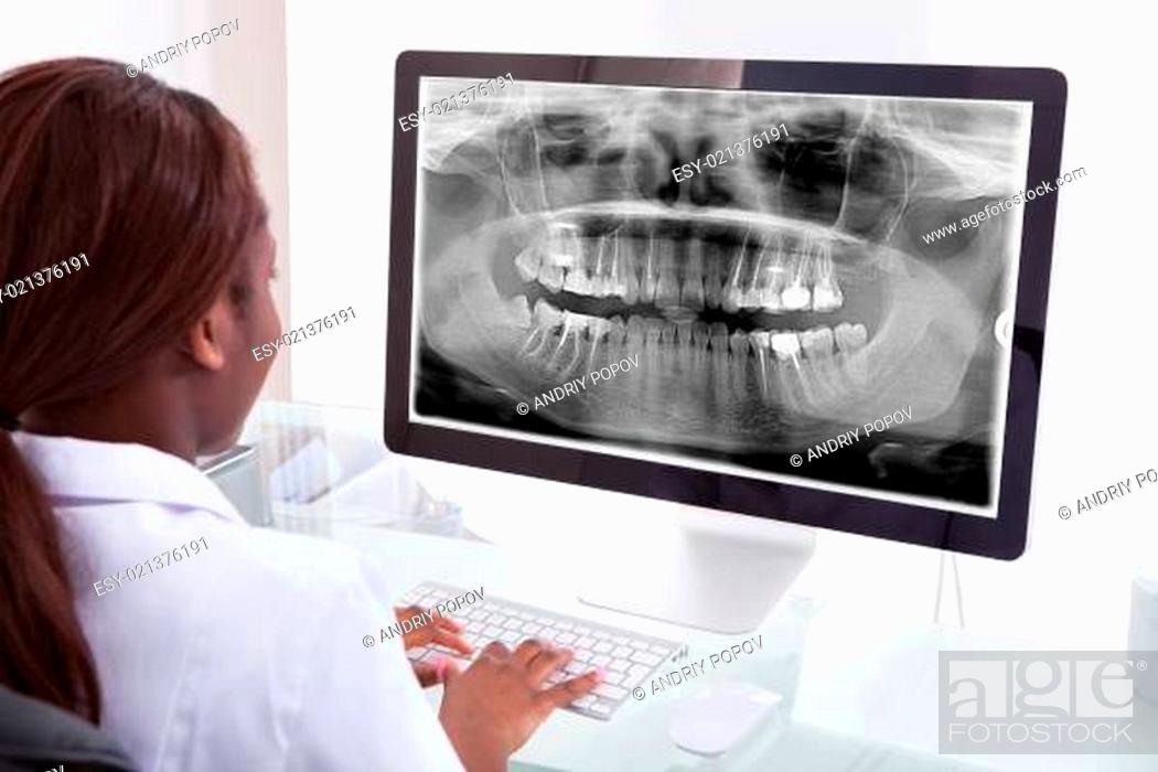 Stock Photo: Female dentist examining jaw Xray on computer in clinic.