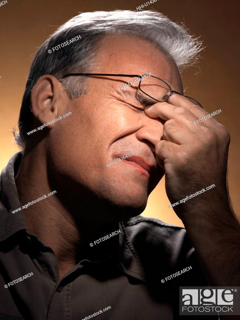 Stock Photo: Tired man rubbing eyes.