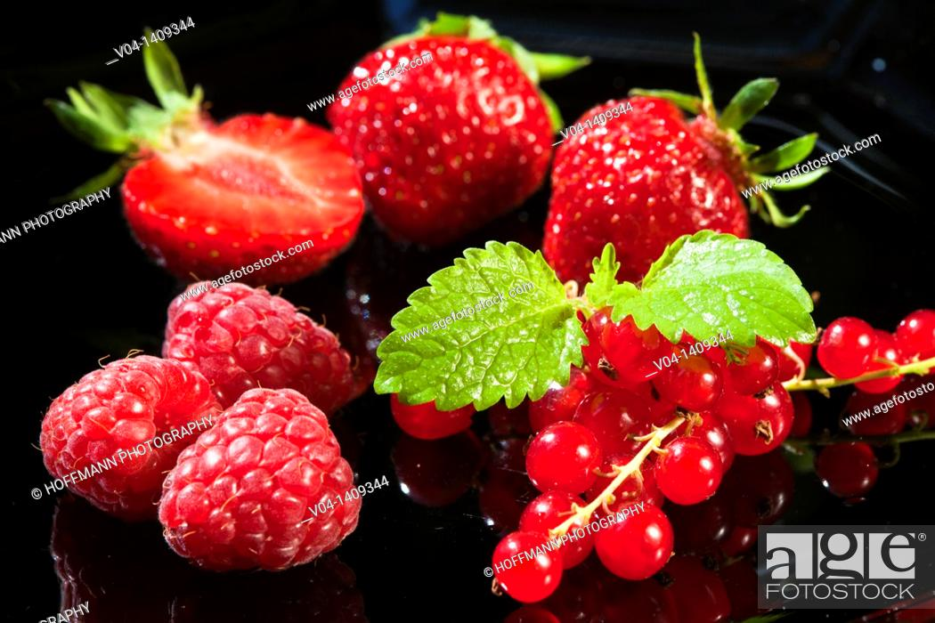 Imagen: Strwaberries, raspberries and redcurrant on a black background.