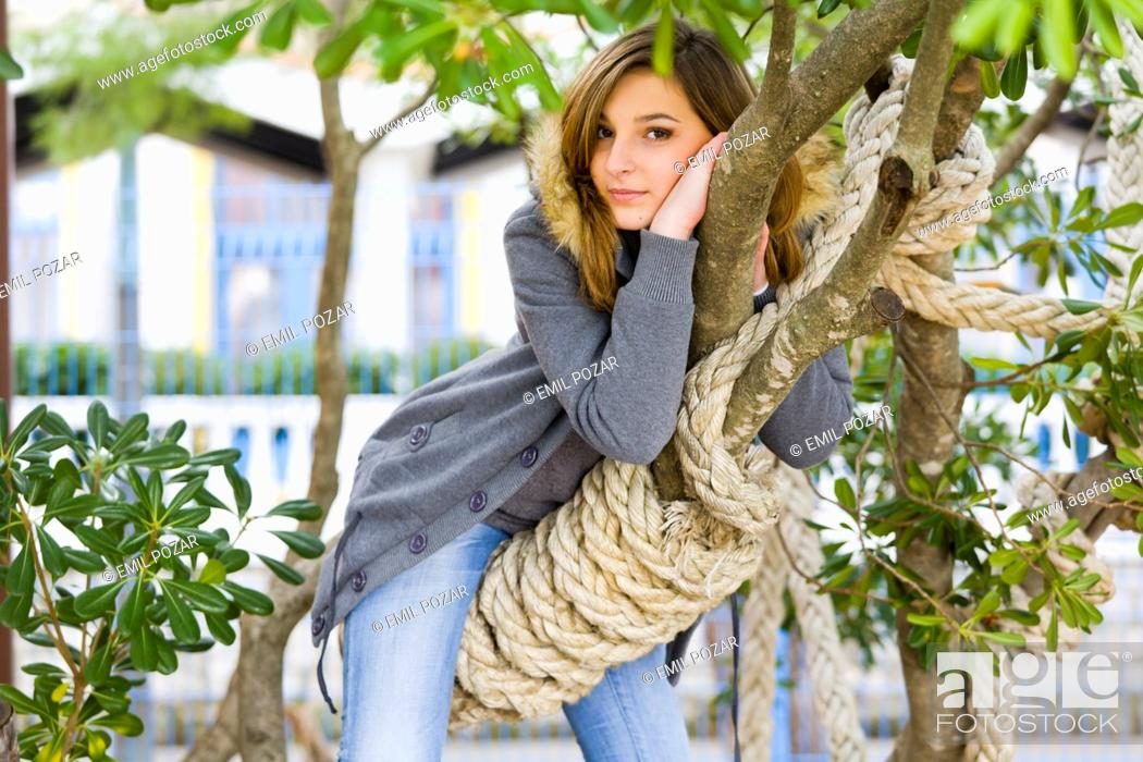 Stock Photo: Young woman riding a tree branch.