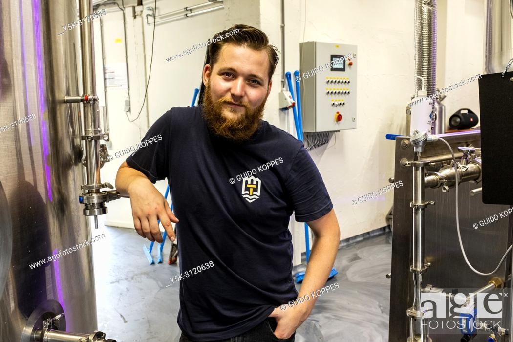 Stock Photo: Tilburg, Netherlands. Portrait of Robin, a male beer brewer inside his newly build city brewery at Stadsbrouwerij 013. Locally produced craftbeers are booming.