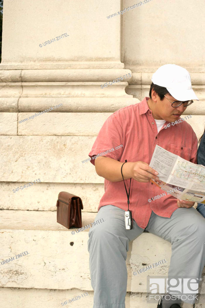 Stock Photo: Asian man sitting on stairs while looking at a map.