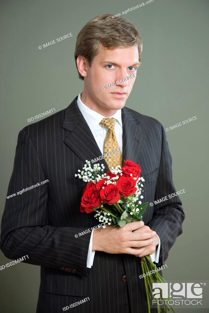 Stock Photo: Portrait of a man holding a bouquet of roses.