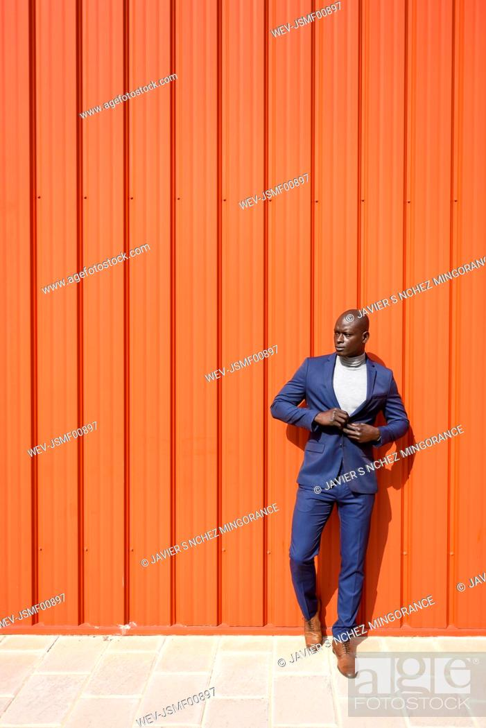 Stock Photo: Portrait of businessman wearing blue suit and grey turtleneck pullover standing in front of orange wall.