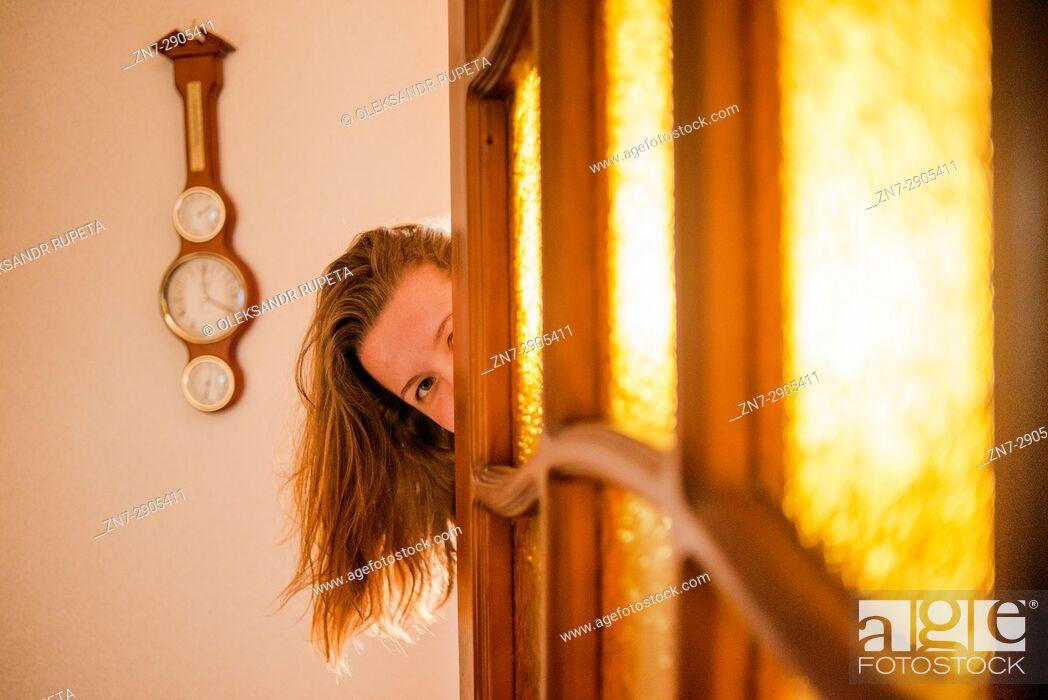 Stock Photo: Girl peeping from behind the door.