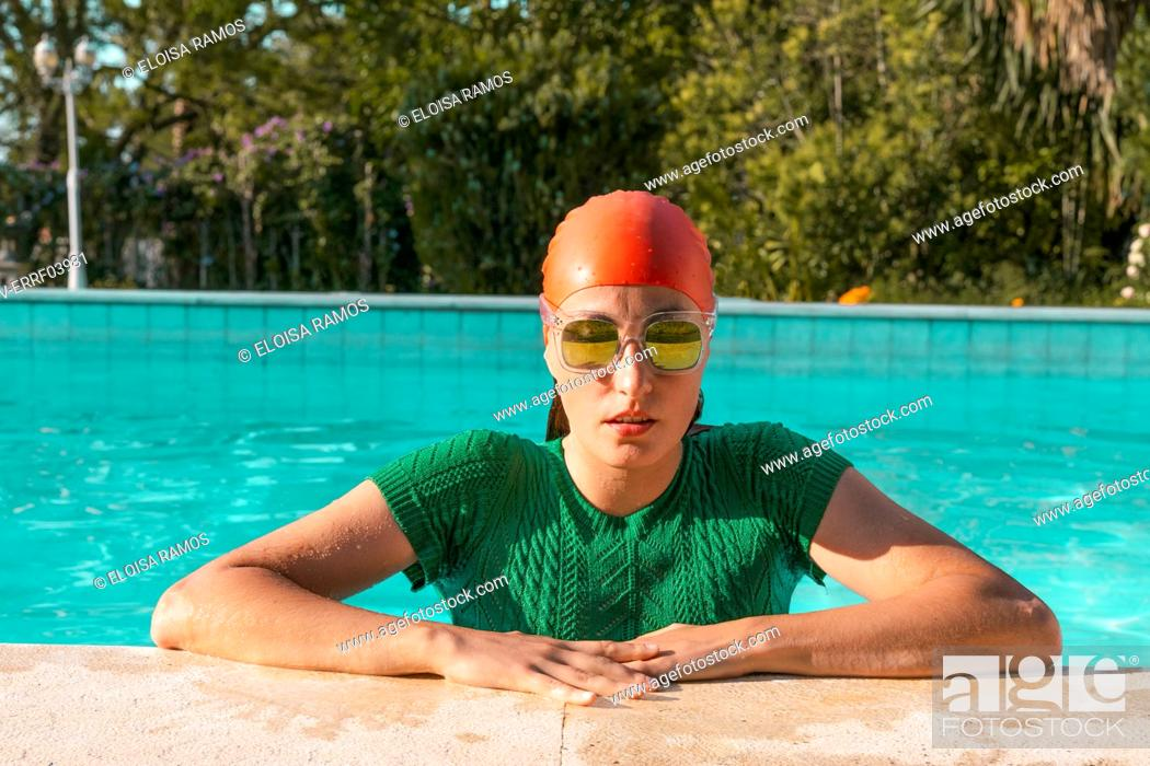 Stock Photo: Portrait of woman leaning on poolside wearing red swimming cap, green knit pullover and mirrored sunglasses.