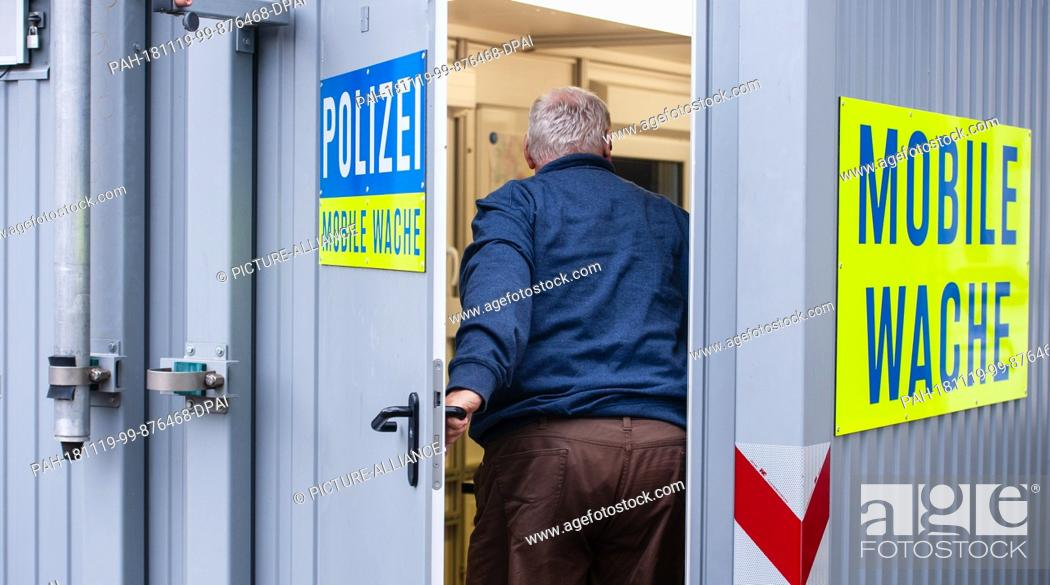 Stock Photo: 19 November 2018, Lower Saxony, Bergen an der Dumme: A man enters the mobile police station in Bergen at the stupid. In Bergen an der Dumme.