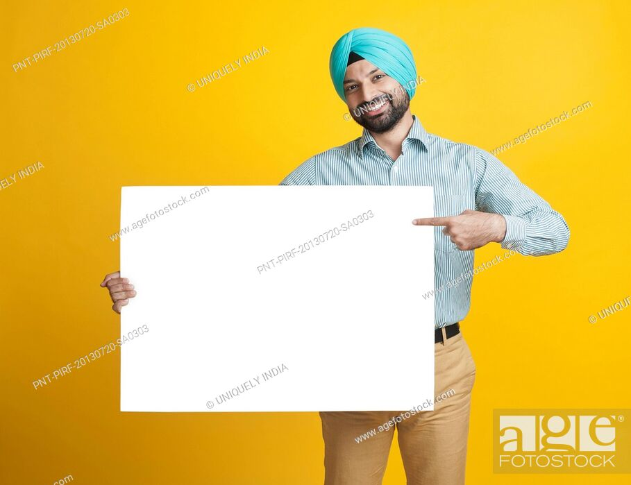 Stock Photo: Portrait of a sikhman holding a blank placard and smiling.