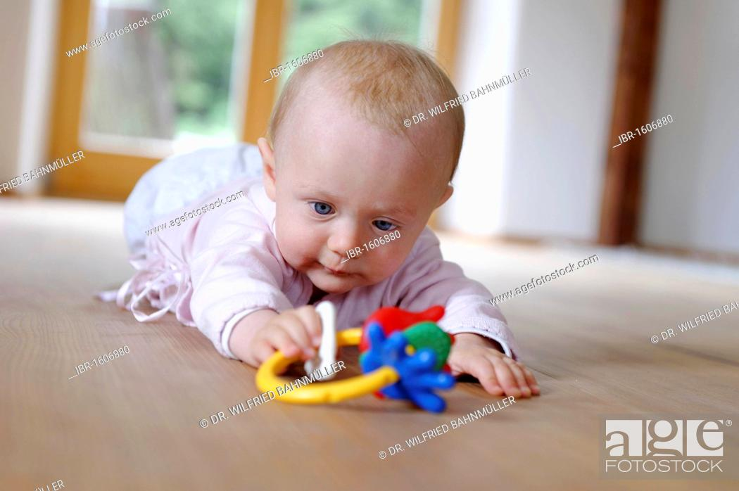 Stock Photo: Small baby, 4 months, lying on her belly, with teether.