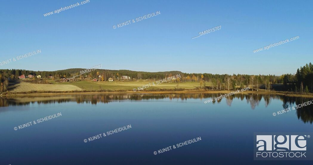 Stock Photo: Aerial shot of a glassy lake with farm houses on a sunny autumn day. Skalmsjö, Bredbyn, Västernorrland, Sweden, Europe.
