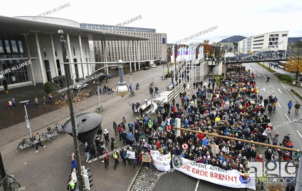 """Stock Photo: 29 November 2019, Baden-Wuerttemberg, Freiburg: On the action day of """"""""Fridays for Future"""""""" thousands of students walk through the city centre with the banner."""