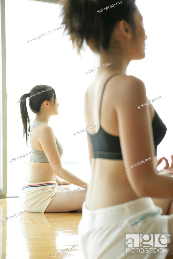 Stock Photo: Two young women cross their legs and sit while they perform yoga in the gym.