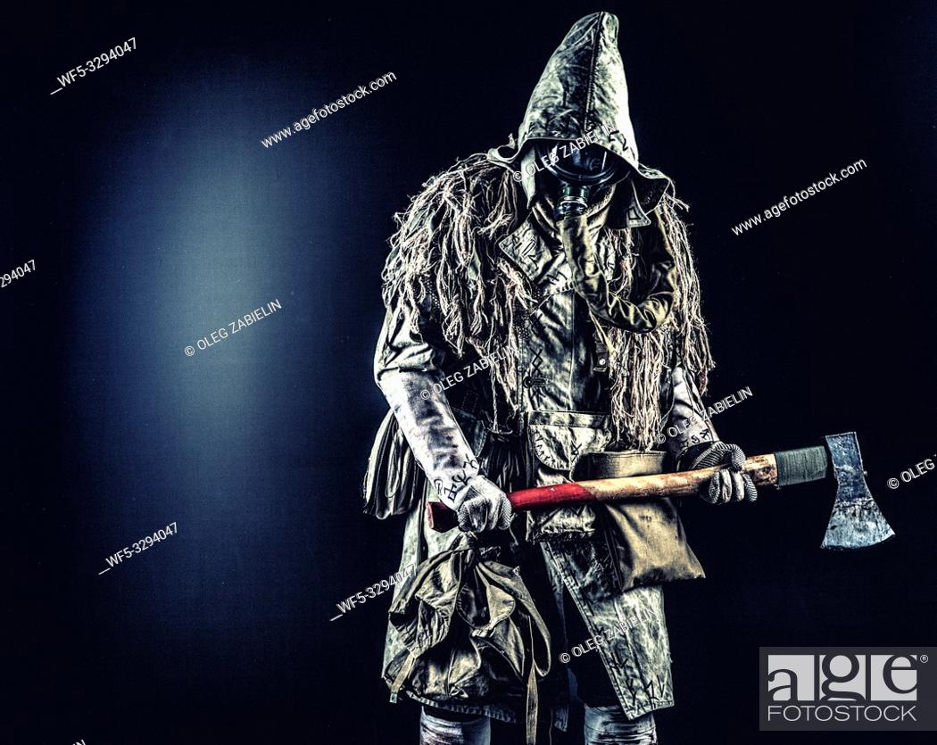 Stock Photo: Post apocalyptic survivor, radioactive zone stalker, crazy serial killer or maniac in gas mask and tattered clothes decorated with runes.