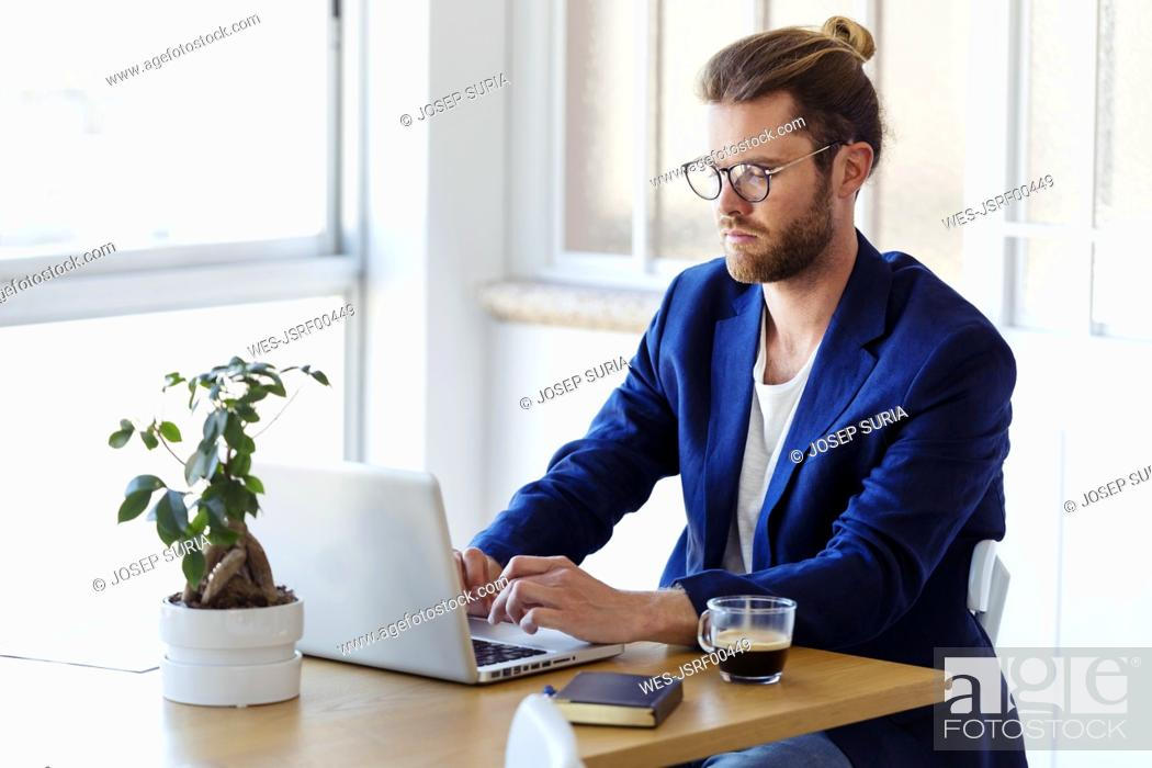 Imagen: Businessman using laptop at table in modern office.
