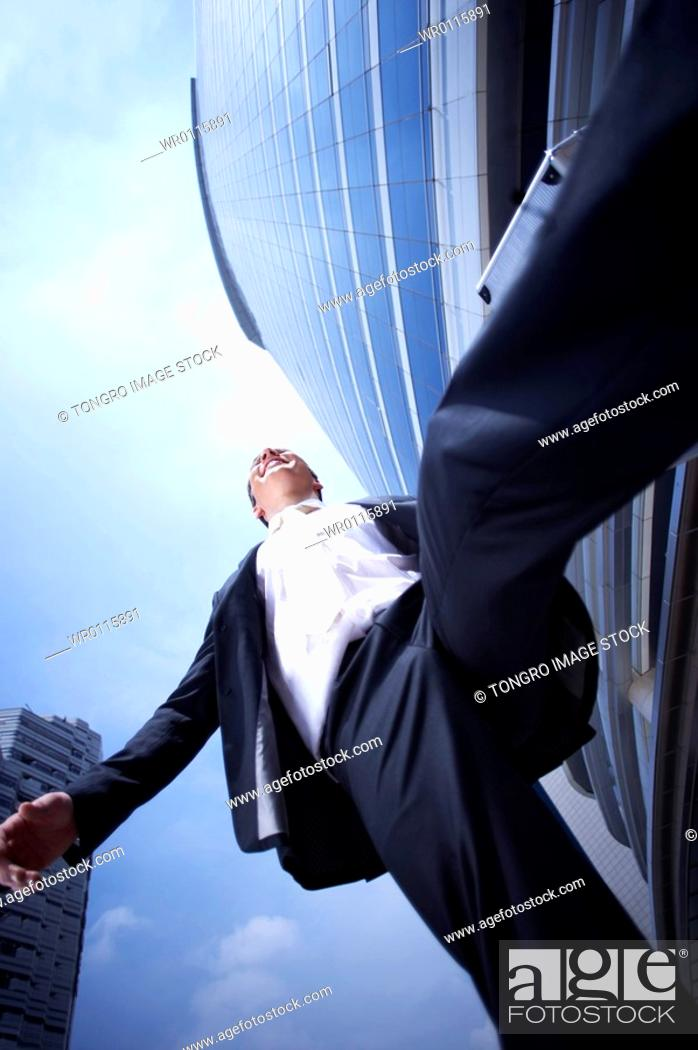 Stock Photo: man running in front of the building at low angle.