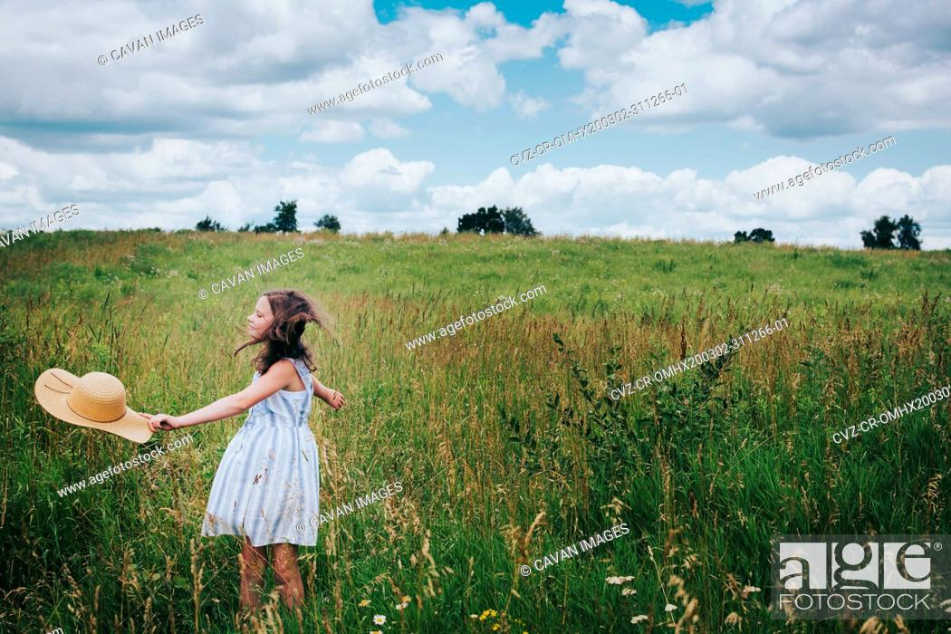 Stock Photo: Teen Girl Twirling in a Grassy Field on a Cloudy Summer Day.