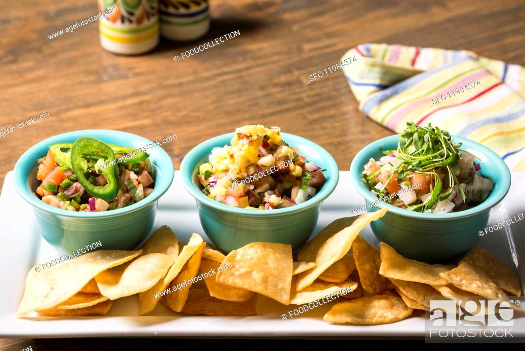 Stock Photo: Three different salsas with tortilla chips.