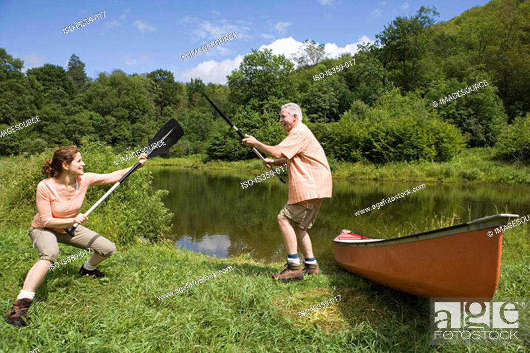 Stock Photo: Mature couple playing with oars.