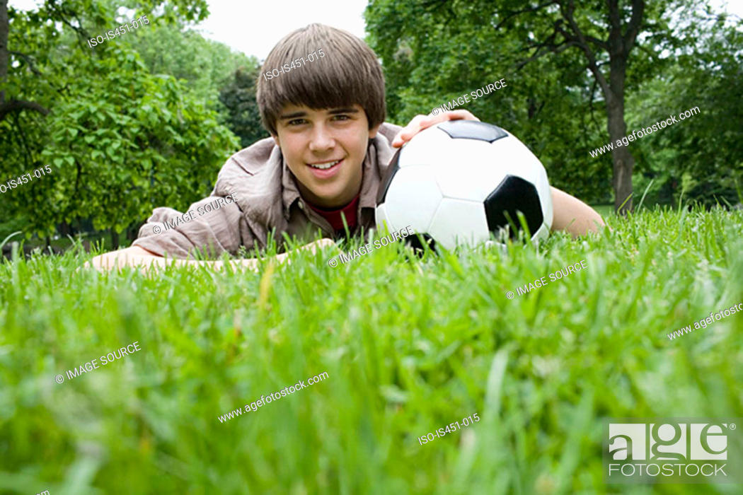 Stock Photo: Teenage boy with a football in park.
