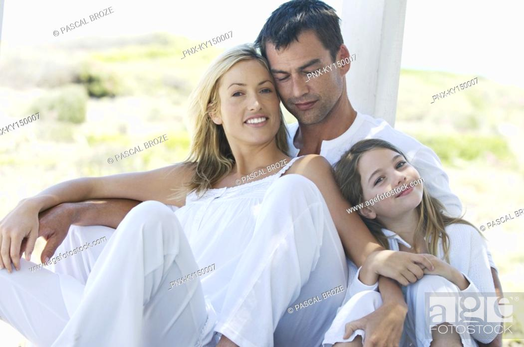 Stock Photo: Parents and daughter smiling for the camera, outdoors.