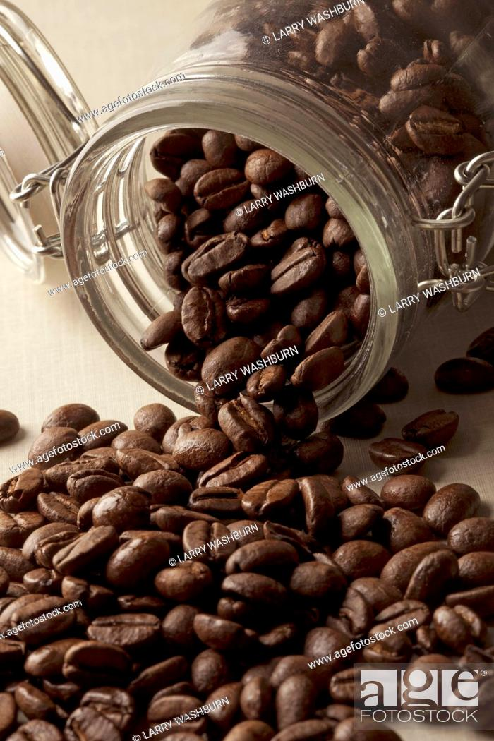 Stock Photo: Detail of coffee beans spilling from a jar.