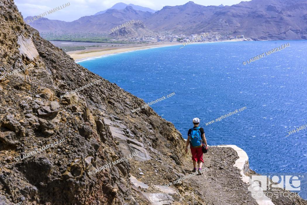 Stock Photo: Woman Hiking between the Ponta Machado Lighthouse (Farol de Dona Amélia) and Sao Pedro Village in the background, Sao Vicente, Cape Verde Islands.