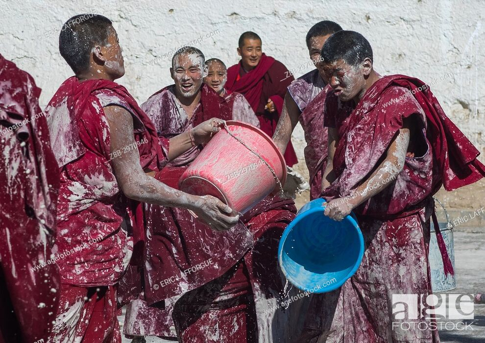 Stock Photo: Tibetan monks enjoying a water fight after the yearly renovation of the Rongwo monastery, Tongren County, Longwu, China.