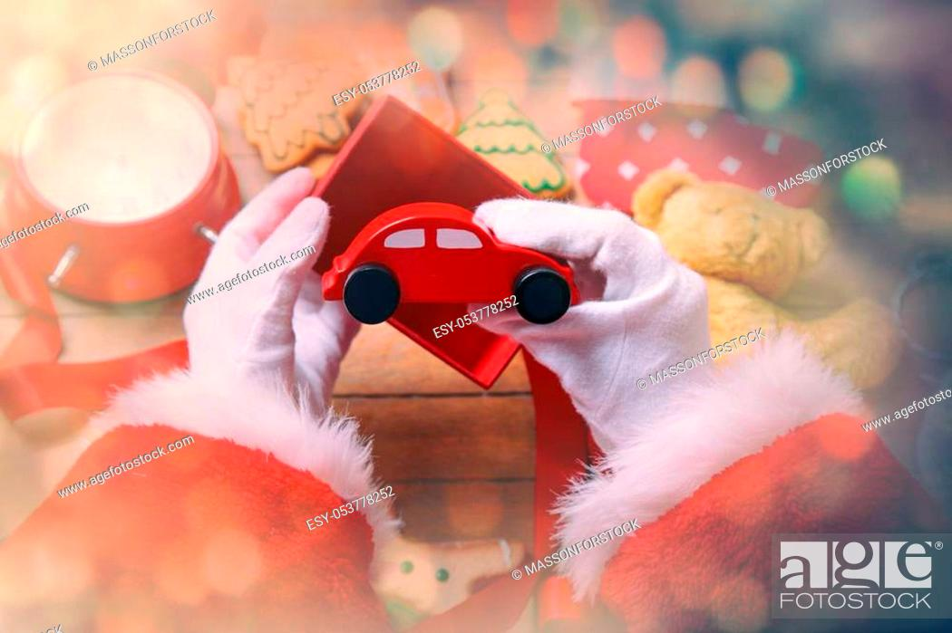 Stock Photo: Santa Claus have wrapping a Christmas toy car and other gifts on wooden background.