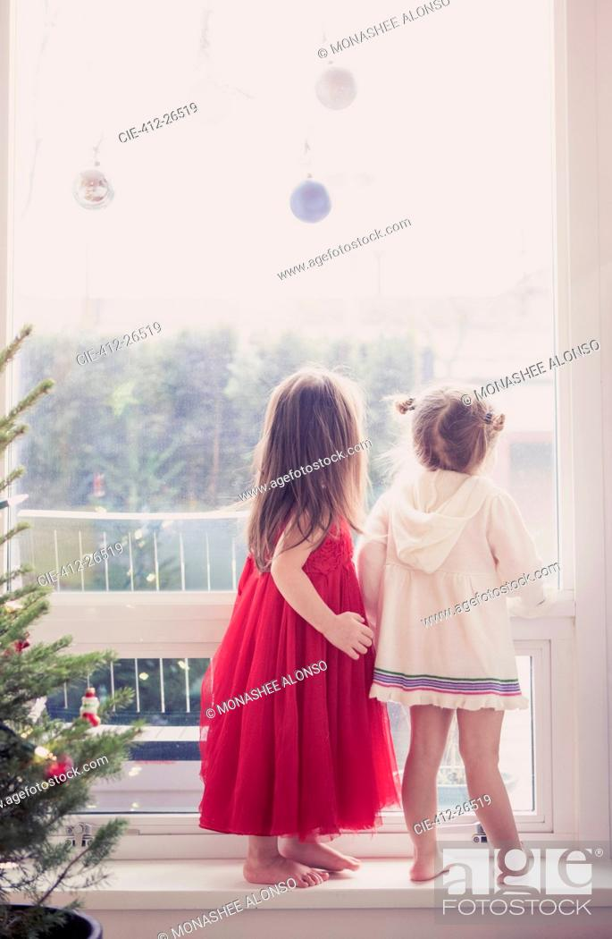 Stock Photo: Girls on window ledge below Christmas ornaments.