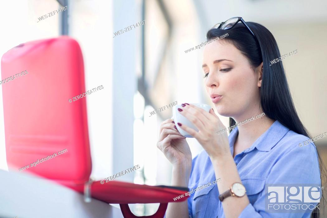 Stock Photo: Employee cooling coffee down before drinking it.