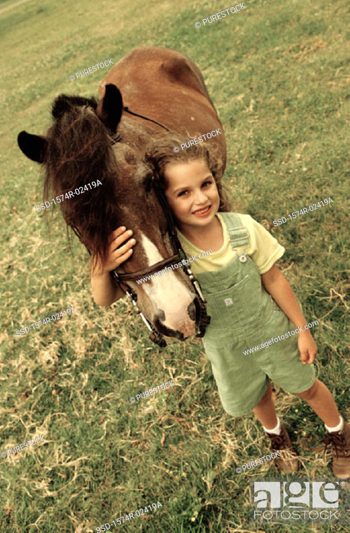Stock Photo: Portrait of a girl standing with a horse.
