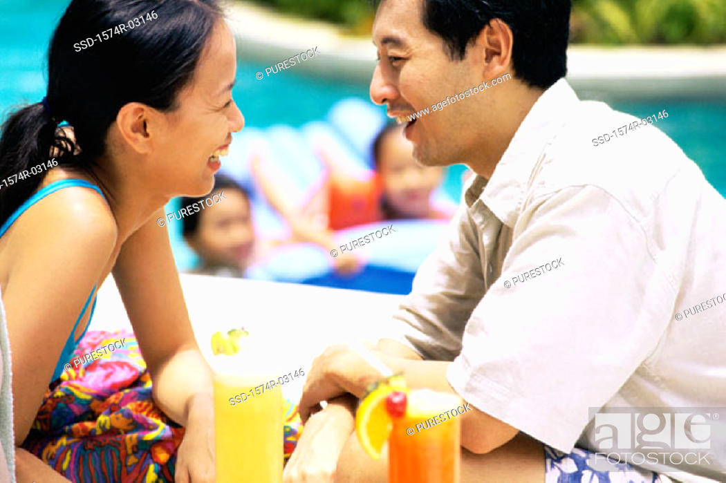 Stock Photo: Parents looking at each other with their children in a swimming pool.