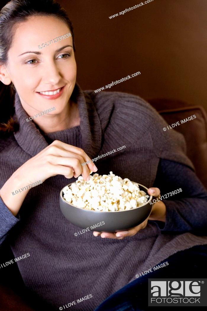 Stock Photo: A mid adult woman eating popcorn.