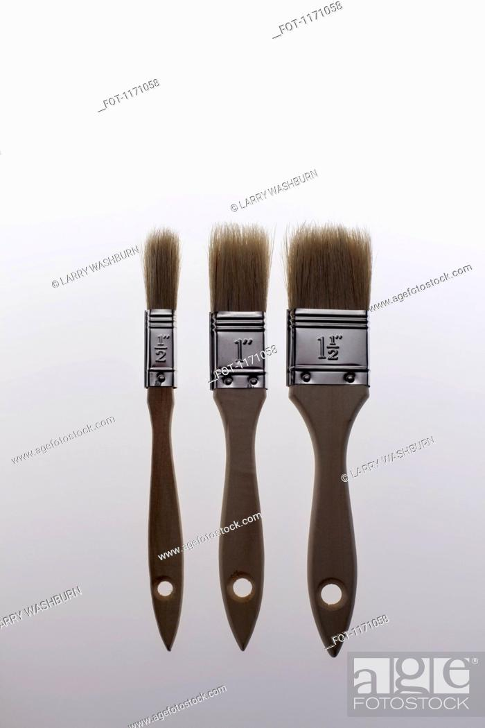 Stock Photo: Three various sized house painting brushes in a row.