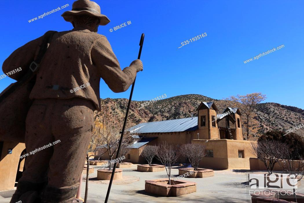 Stock Photo: The statue of a pilgrim in the garden of historical catholic chapel of Santuario de Nuestro Senor de Esquipulas aka El Santuario de Chimayo.