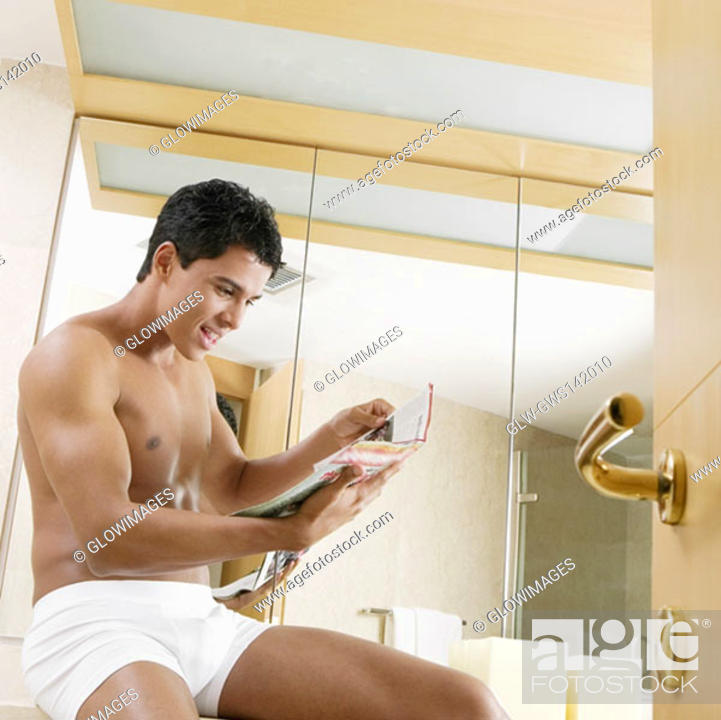 Stock Photo: Side profile of a young man sitting in the bathroom and reading a magazine.