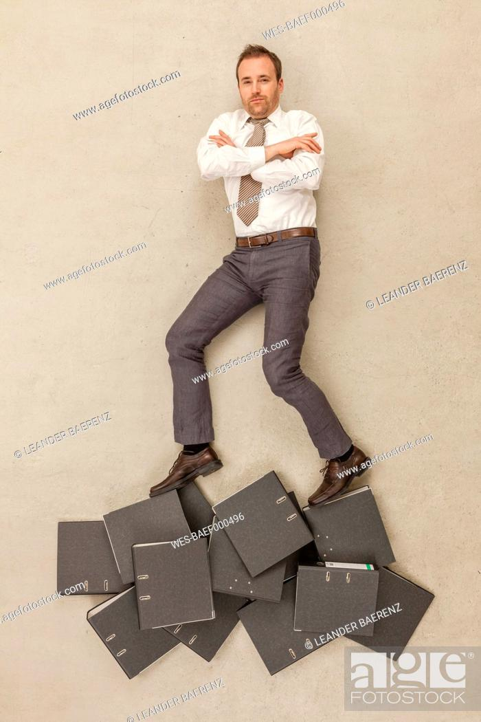 Stock Photo: Businessman standing above files.