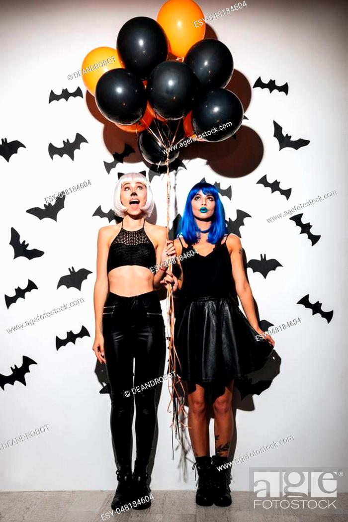 Stock Photo: Image of two emotional young women in halloween costumes on party over white background with balloons. Looking aside.