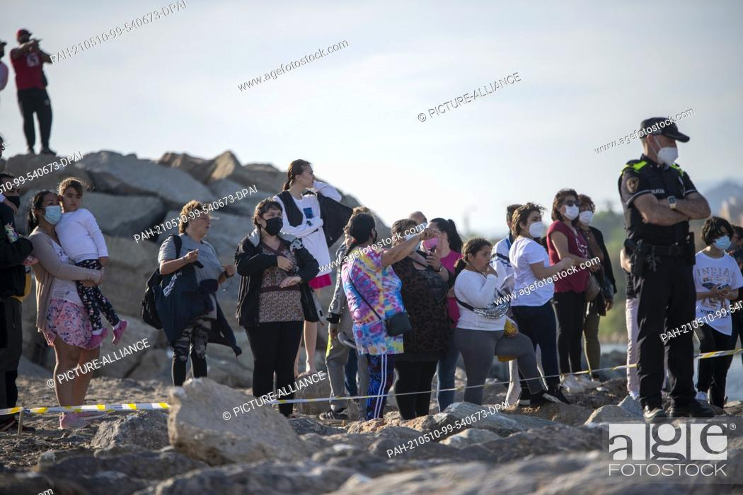 Stock Photo: 08 May 2021, Spain, Barcelona: Beachgoers and onlookers watch the movements of a grey whale behind the police cordon. A young grey whale.