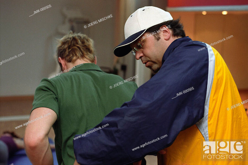 Stock Photo: Young man at the fitness studio, gym, working out, doing exercises at an athletic implement, instructed by a coach, trainer.